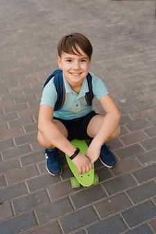 Lächelnder junge, der auf skateboard in der stadt spielt, kaukasisches kind, das penny board reitet