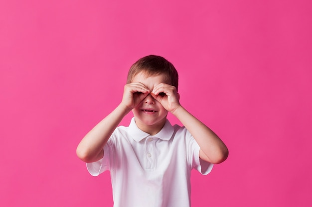 Lächelnder junge, der durch finger als ferngläser über rosa hintergrund schaut