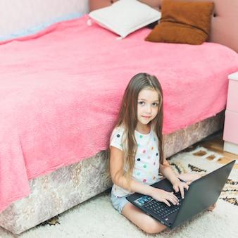 Lächelnder junge, der im schlafzimmer unter verwendung des laptops sitzt