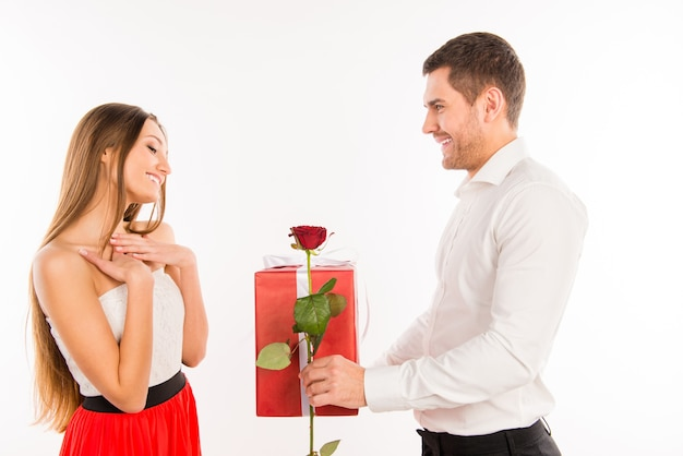 Lächelnder junge, der seiner freundin ein geschenk und eine rose gibt