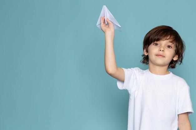 Lächelnder junge der vorderansicht im weißen t-shirt, das papierflugzeug auf blauem schreibtisch hält
