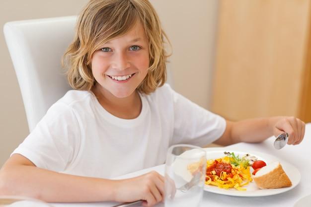 Lächelnder junge, der zu abend isst