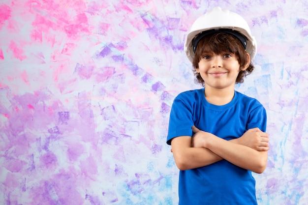 Lächelnder junge im blauen t-shirt und im weißen helm auf mehrfarbigem