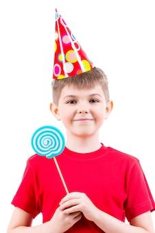 Lächelnder junge im roten t-shirt und im partyhut, die farbige süßigkeiten halten - lokalisiert auf weiß.