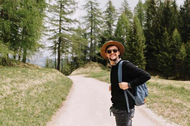 Lächelnder junge im schwarzen hemd und im hut, die auf waldstraße aufwerfen, die reise im urlaub genießt