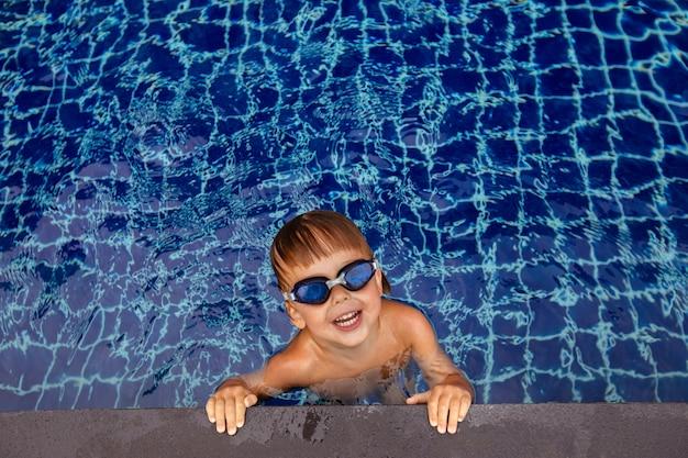 Lächelnder junge in den schutzbrillen im wasser nahe rand des pools