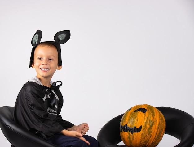Lächelnder junge in einem fledermauskostüm. komposition für halloween, foto auf einer weißen wand. bereit für den urlaub.