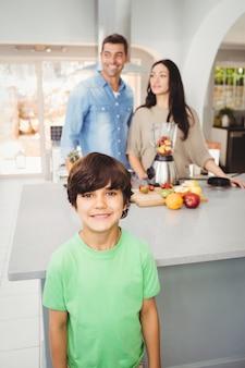 Lächelnder junge mit den eltern, die fruchtsaft zubereiten