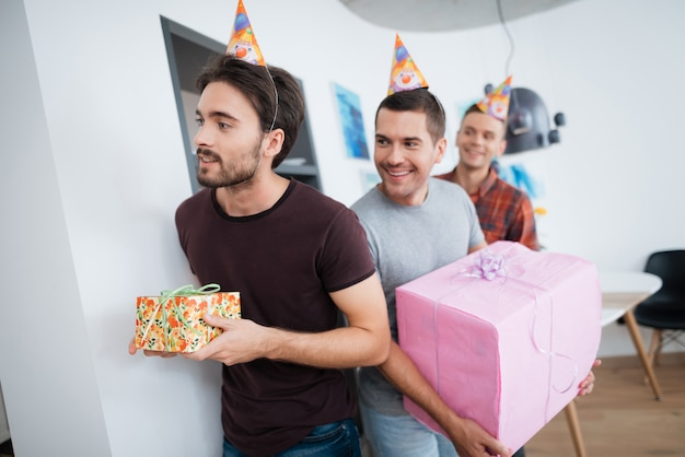 Lächelnder junge mit geschenkbox. überraschungsgeburtstagsparty.