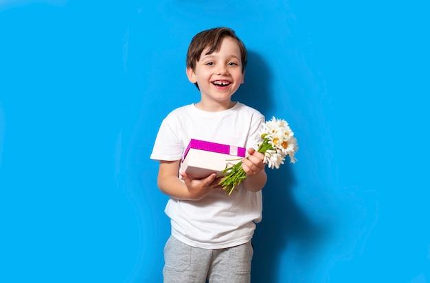 Lächelnder junge mit geschenkgeschenkbox in seinen händen und blumenstrauß