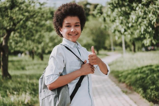 Lächelnder junge mit rucksack zeigen daumen oben im park.