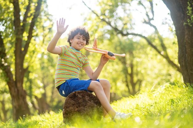 Lächelnder junge mit spielzeugflugzeug im park