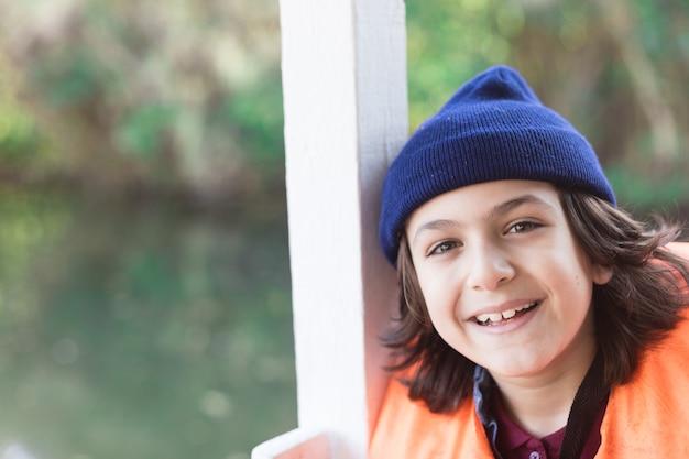 Lächelnder junge mit strickmütze
