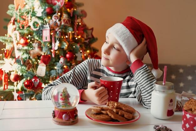 Lächelnder junge mit weihnachtsroter tasse tee am christmass baum. familie mit kindern feiern winterferien. heiligabend zu hause. kinderjunge in der weihnachtsküche. junge in nikolausmütze.