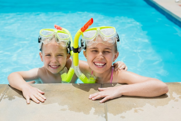 Lächelnder junge und mädchen, die auf der seite des schwimmbades entspannen