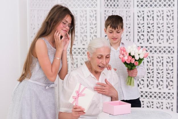 Lächelnder junge und mädchen, die hinter überraschter großmutter stehen