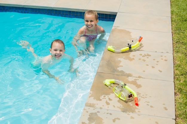 Lächelnder junge und mädchen, die im schwimmbad spielen