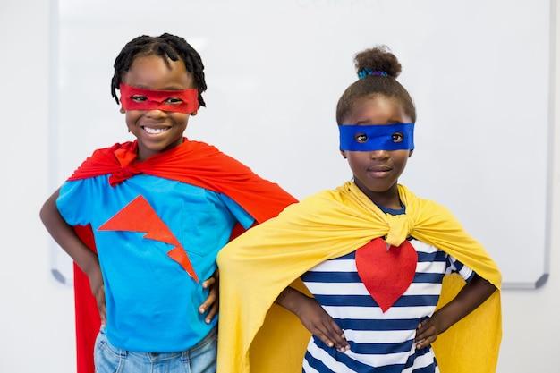Lächelnder junge und mädchen, die vortäuschen, ein superheld zu sein