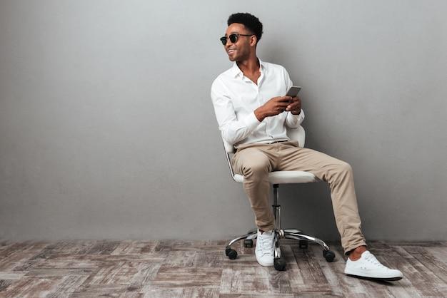 Lächelnder junger afrikanischer mann, der in einem stuhl sitzt