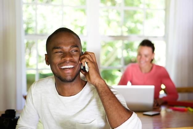Lächelnder junger afrikanischer mann, der zu hause am handy spricht