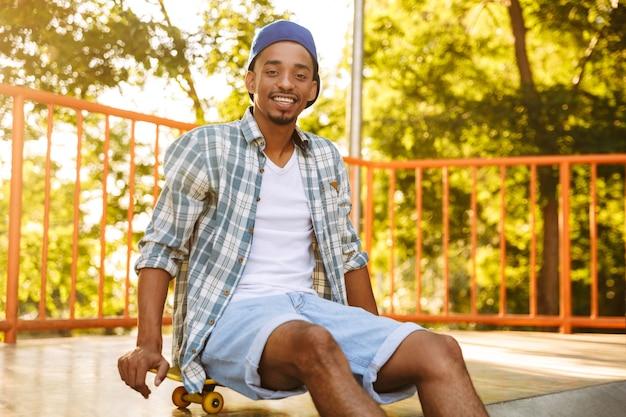Lächelnder junger afrikanischer mann mit skateboard