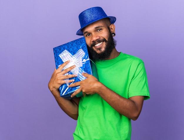 Lächelnder junger afroamerikaner mit partyhut, der eine geschenkbox um das gesicht hält