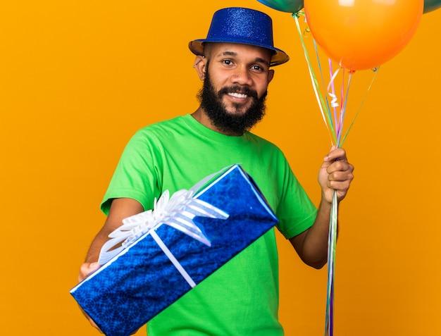 Lächelnder junger afroamerikaner mit partyhut, der luftballons hält und eine geschenkbox in die kamera hält