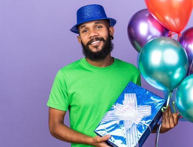 Lächelnder junger afroamerikaner mit partyhut, der luftballons mit geschenkbox hält