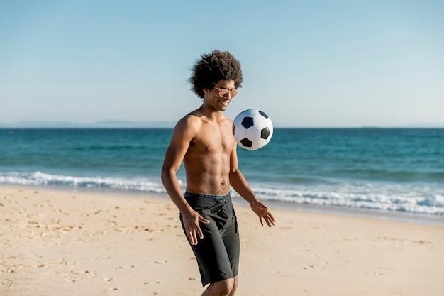 Lächelnder junger afroamerikanermann, der fußball auf seeküste spielt