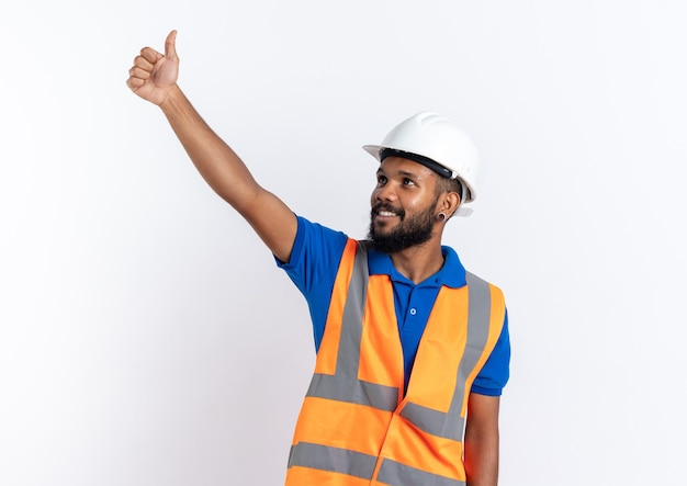 Lächelnder junger afroamerikanischer baumeister in uniform mit schutzhelm, der nach oben auf die seite schaut, die auf weißem hintergrund mit kopienraum isoliert ist