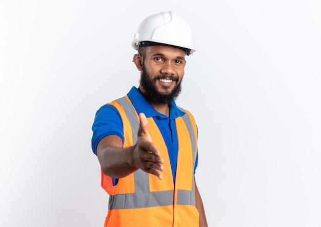 Lächelnder junger afroamerikanischer baumeister in uniform mit schutzhelm, der seine hand isoliert auf weißem hintergrund mit kopierraum hält