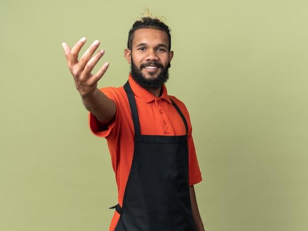 Lächelnder junger afroamerikanischer friseur in uniform, der die hand in richtung ausstreckt