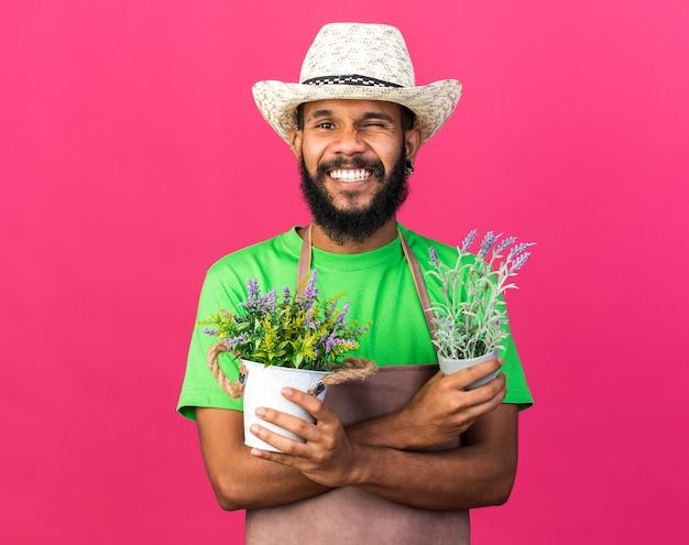 Lächelnder junger afroamerikanischer gärtner mit gartenhut, der blumen im blumentopf hält und überquert, isoliert auf rosa wand