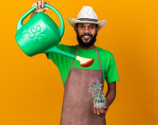Lächelnder junger afroamerikanischer gärtner mit gartenhut, der blumen im blumentopf mit gießkanne gießt