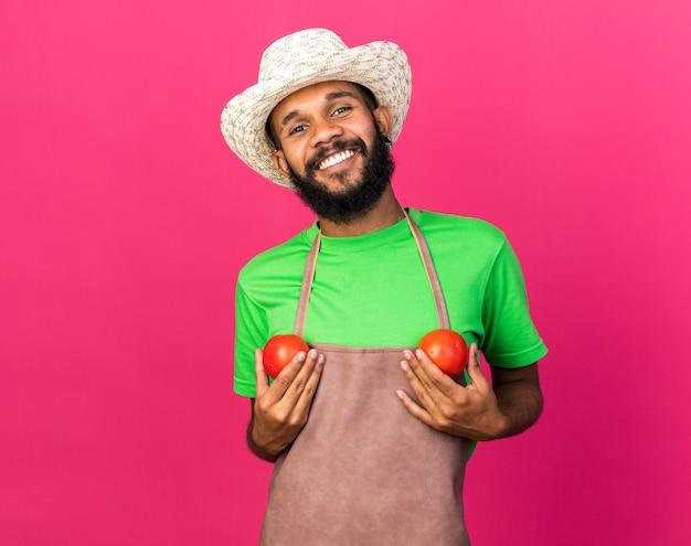 Lächelnder junger afroamerikanischer gärtner mit gartenhut, der tomaten isoliert auf rosa wand hält