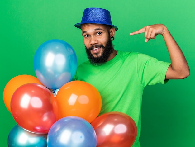 Lächelnder junger afroamerikanischer kerl mit partyhut, der auf luftballons zeigt und zeigt