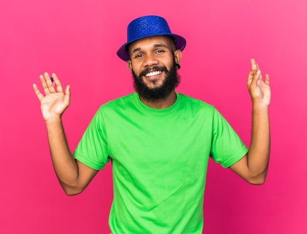 Lächelnder junger afroamerikanischer kerl mit partyhut, der eine partypfeife hält, die eine gute geste einzeln auf rosa wand zeigt