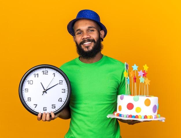 Lächelnder junger afroamerikanischer kerl mit partyhut, der kuchen mit wanduhr hält