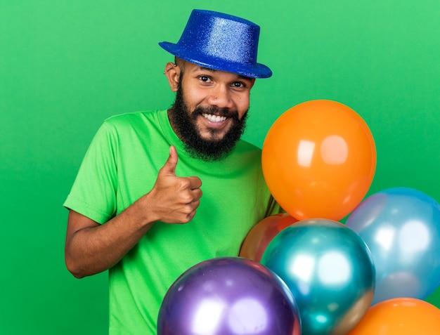 Lächelnder junger afroamerikanischer kerl mit partyhut, der luftballons hält, die daumen nach oben zeigen, isoliert auf grüner wand