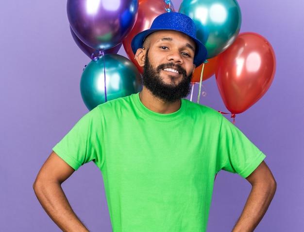 Lächelnder junger afroamerikanischer kerl mit partyhut, der vor ballons steht, isoliert auf blauer wand