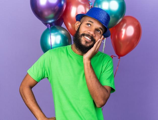 Lächelnder junger afroamerikanischer kerl mit partyhut, der vor ballons steht und hand auf das kinn legt