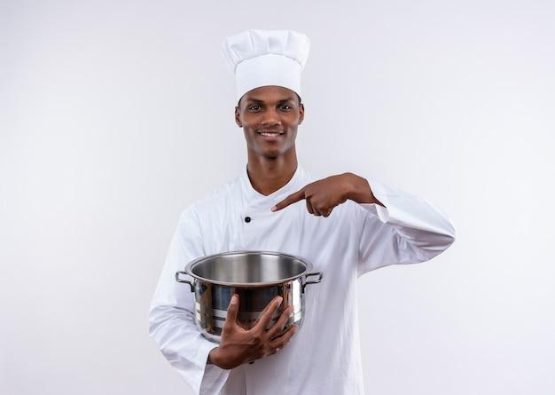 Lächelnder junger afroamerikanischer koch in der kochuniform hält topf und punkte am topf auf lokalisiertem weißem hintergrund mit kopienraum