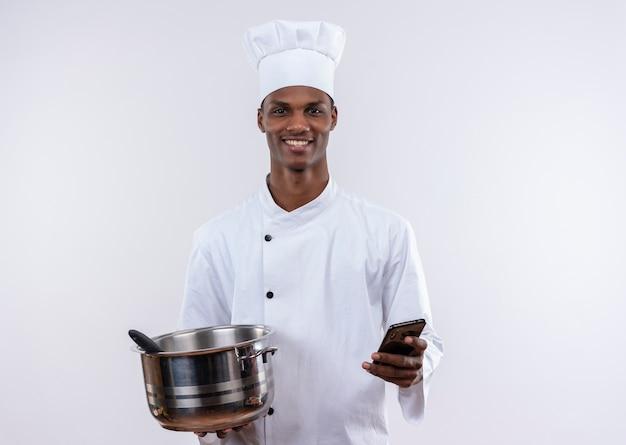 Lächelnder junger afroamerikanischer koch in der kochuniform hält topf und telefon auf lokalisiertem weißem hintergrund mit kopienraum
