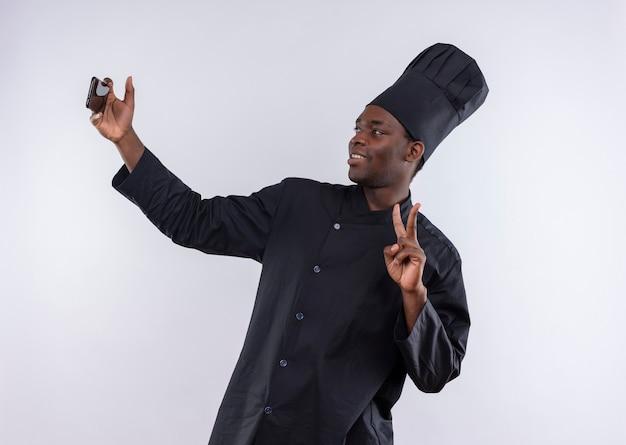 Lächelnder junger afroamerikanischer koch in der kochuniform schaut auf telefon und gestikuliert siegeszeichen auf weiß mit kopienraum