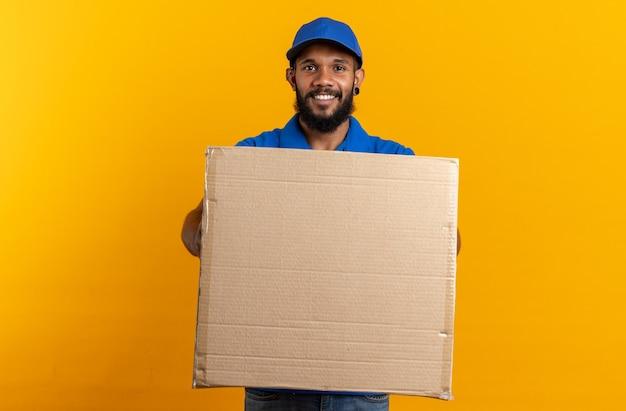 Lächelnder junger afroamerikanischer lieferbote, der einen großen karton isoliert auf einer orangefarbenen wand mit kopierraum hält