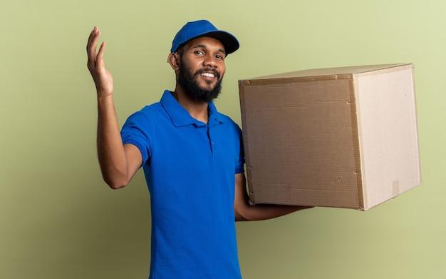 Lächelnder junger afroamerikanischer lieferbote, der einen karton mit erhobener hand hält, isoliert auf olivgrüner wand mit kopierraum standing