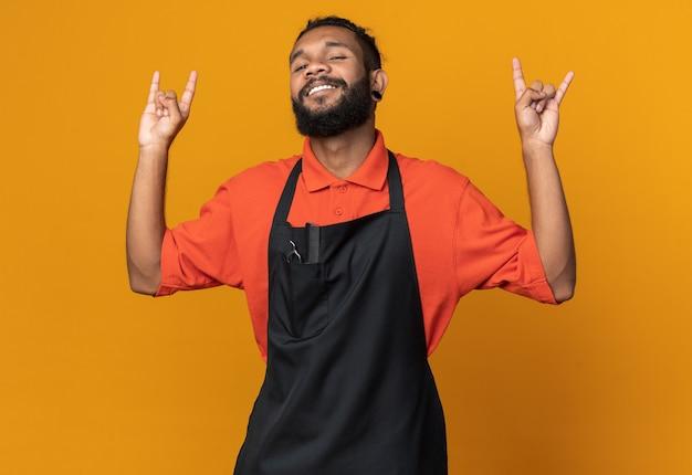 Lächelnder junger afroamerikanischer männlicher barbier in uniform, der rock-schild auf oranger wand isoliert tut