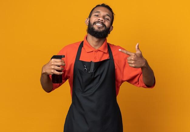 Lächelnder junger afroamerikanischer männlicher friseur, der eine uniform trägt und auf haarspray zeigt?