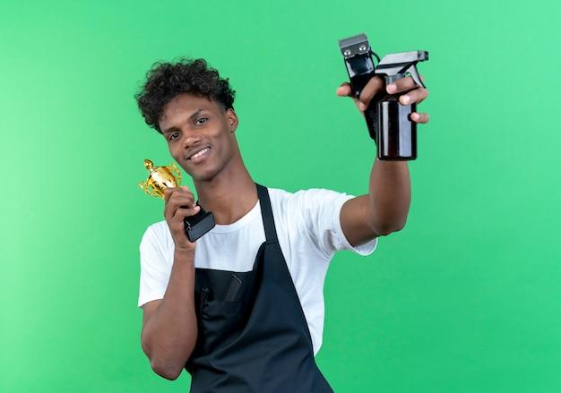Lächelnder junger afroamerikanischer männlicher friseur, der uniform trägt, die siegerpokal um gesicht hält und friseurwerkzeuge auf grüner wand lokalisiert