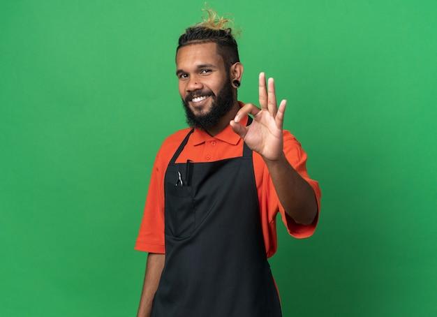 Lächelnder junger afroamerikanischer männlicher friseur in uniform, der ein gutes zeichen macht